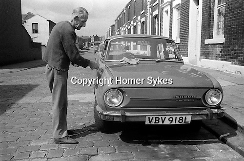 Working class white male painting over rust damage on his Skoda car Blackburn Lancashire  1983. Typical cobbled street terraced houses.