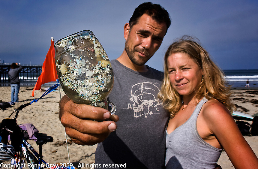 "Saturday, June 21 2009.  Pacific Beach, San Diego, CA, USA:  Dr Marcus Eriksen and Anna Cummins of the environmental group Algalita Marine Research Foundation (AMRF) display a bottle of ""plastic soup"" shortly after arriving in PB at the conclusion of a six-week journey from Vancouver to TJ to raise awareness about marine debris.   The couple spoke at 40 different events along the way and presented 5 mayors with samples of the ""plastic soup"" that they collected form a remote part of the Pacific Ocean known as the North Pacific Gyre.  The confluence of currents in that area of the Pacific has created a high concentration of marine debris - particularly plastics - that is clogging the area, endangering marine life and entering our food chain."