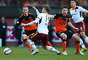 Motherwell's Lee Erwin is pulled back by Dundee Utd's Callum Morris .