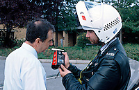 Traffic motorcycle police officer breathalysing a motorist. The officer is using a handheld Lion Alcometer breathalyser called an SL2. This image may only be used to portray the subject in a positive manner..©shoutpictures.com..john@shoutpictures.com