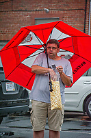 Man eating popcorn while standing under red umbrella during rain storm.