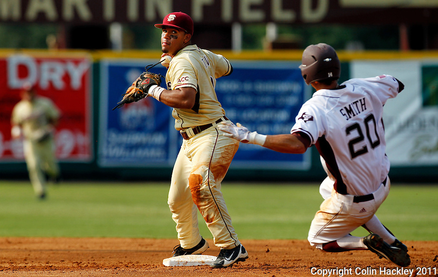 TALLAHASSEE, FL 10-FSU-TAMUBASE11 CH-Florida State's Devon Travis turns a double play as Texas A&M's Adam Smith tries to slide to second, Sunday at Dick Howser Stadium during NCAA Super Regional action in Tallahassee. The Seminoles beat the Aggies 23-9 to stay alive in the best of three series...COLIN HACKLEY PHOTO