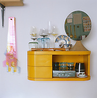 A small yellow wall cabinet in the kitchen houses a collection of glasses and an ornately painted teacup and saucer
