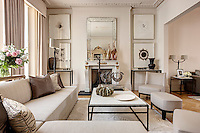 A traditional sitting room with a marble fireplace and plasterwork cornice. The room is furnished with a modern corner sofa upholstered in neutral tones and a metal coffee table.