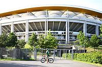 16th May 2020, Commerzbank-Arena, Frankfurt, Germany; Bundesliga football, Eintracht Frankfurt versus Borussia Moenchangladbach; A cyclist stands in front of the locked gate of the Commerzbank Arena at the ghost game Frankfurt versus Moenchengladbach