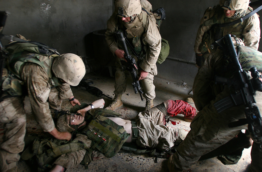 Members of Kilo Co. 3rd BN 1st Marines rush to evacuate PFC Alex Nicoll to safety before he bleeds to death for gunshot wounds to his left leg on Nov. 13, 2004 during the assault on Fallujah.