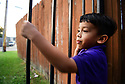 Christopher Mejia looks for his father from the gate of his grandmother's home in Metairie, La. He misses his father, Erlin San Martin, who has been detained by immigration authorities.