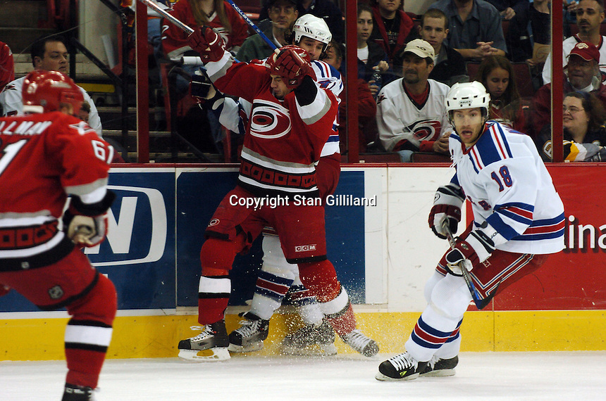 Carolina Hurricanes' Chad Larose, center, checks the New York Rangers' Jed Ortmeyer, behind, as Dominic Moore (18) watches the puck Tuesday, March 14, 2006 at the RBC Center in Raleigh, NC. Carolina won 5-3.