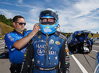Jun 19, 2016; Bristol, TN, USA; A crew member helps NHRA funny car driver Tommy Johnson Jr put on safety gear during the Thunder Valley Nationals at Bristol Dragway. Mandatory Credit: Mark J. Rebilas-USA TODAY Sports