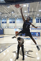 NWA Democrat-Gazette/ANDY SHUPE<br /> Austin Garrett (top), a basketball player at Fayetteville High School, leaps Tuesday, Sept. 18, 2018, over teammate Isaiah Releford as he dunks the ball while participating in the dunk contest during the first Campaign Tipoff for the United Way of Northwest Arkansas' campaign in Wildcat Arena at Har-Ber High School in Springdale. This year's goal for the agency is approximately $1.8 million