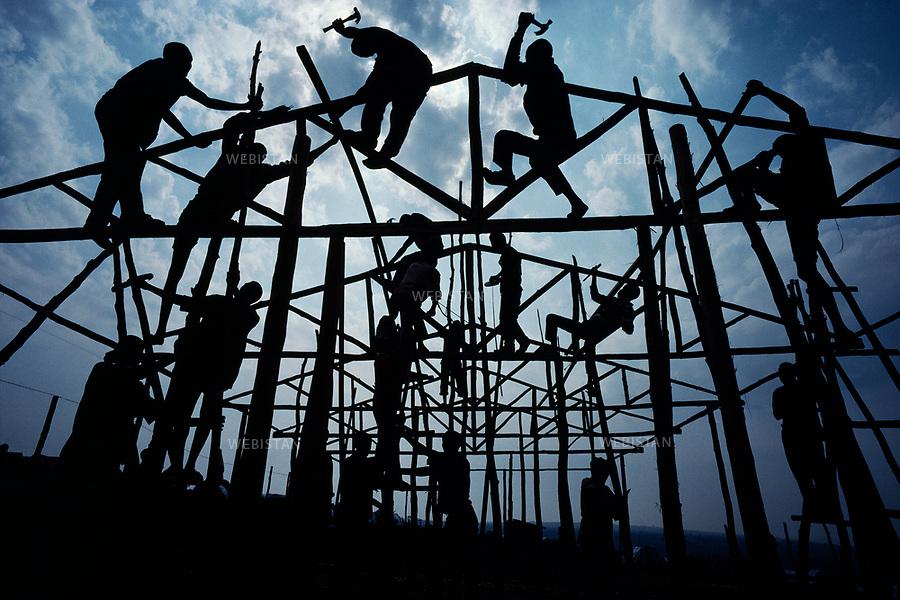 Burundi. Lake Cyohoha. Maza Camp. 1994. During the Rwandan Genocide, a group of refugees build a structure for a new building. Burundi. Lac Cyohoha. Camp de Maza. Pendant le génocide au Rwanda, un groupe de réfugiés construit la structure d'un nouveau baraquement.