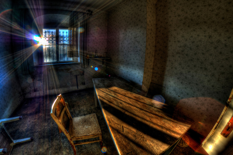 Abandoned room interior with chair and desk and sunlight from behind