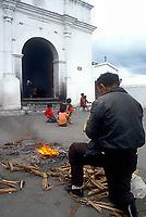 Man praying by fire, smoke keeps away evil spirits, central Guatemala