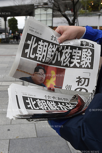 A passerby picks up a special edition newspaper in Ginza, Tokyo, Japan on January 6th, 2016., carrying the news that North Korea has tested a hydrogen bomb. North Korean media on Wednesday morning reported claims that North Korea had successfully detonated a hydrogen bomb at 10am local time. The test was also linked to an artificial earthquake of magniture 5.1 near the purported test site of Punggye-ri. (Photo by Shingo Ito/AFLO)