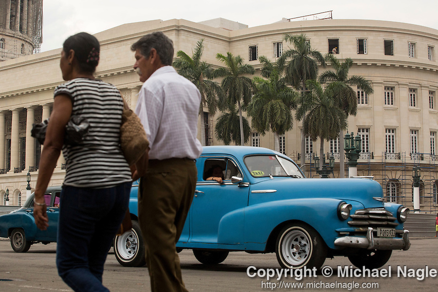 HAVANA, CUBA -- MARCH 24, 2015:   A classic car taxi passes the National Capitol Building in Havana, Cuba on March 24, 2015. Photograph by Michael Nagle