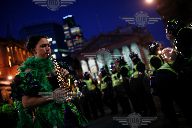 A woman plays a saxophone in front of riot police as thousands of protestors descended on the City of London ahead of the G20 summit of world leaders to express anger at the economic crisis, which many blame on the excesses of capitalism.