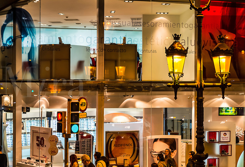 Modern shopping stores with traditional street lamp, Barcelona, Spain