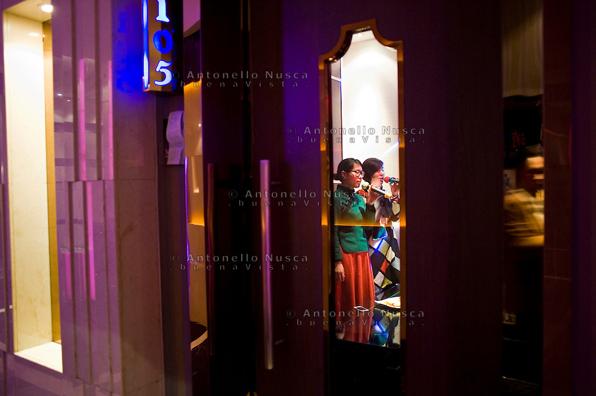 Due ragazze cantano in un karaoke.<br /> Singing in a karaoke