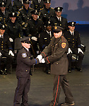 WATERBURY, CT-012318JS25--Wolcott Police Officer Zachary Williams, right, son of late Waterbury Police Officer Walter Williams, presents the Williams Award to Waterbury Police recruit Michael Gigliotti during graduation exercises for the Waterbury Police Department and Waterbury Police Academy's class 2017-01 Tuesday at the Palace Theater in Waterbury. 29 new officers were sworn in during the event. <br /> Jim Shannon Republican-American