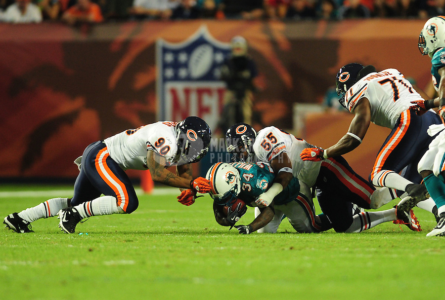 Nov. 18, 2010;  Miami, FL, USA; Miami Dolphins running back (34) Ricky Williams is tackled by Chicago Bears defensive end (90) Julius Peppers and linebacker (55) Lance Briggs at Sun Life Stadium. Mandatory Credit: Mark J. Rebilas-