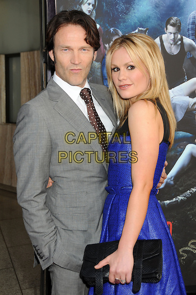 "STEPHEN MOYER & ANNA PAQUIN.HBO's ""True Blood"" Season 3 Premiere held at Arclight Cinemas Cinerama Dome, Hollywood, California, USA..June 8th, 2010.half length dress clutch bag black blue sleeveless leather hand in pocket grey gray suit couple side brown polka dot tie.CAP/ADM/BP.©Byron Purvis/AdMedia/Capital Pictures."