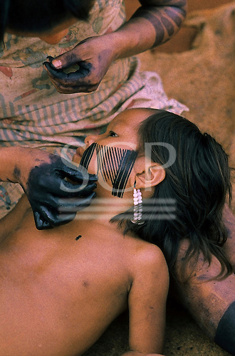 A-Ukre, Brazil. Kayapo Indian mother painting an intricate design on her child's face. Para State.