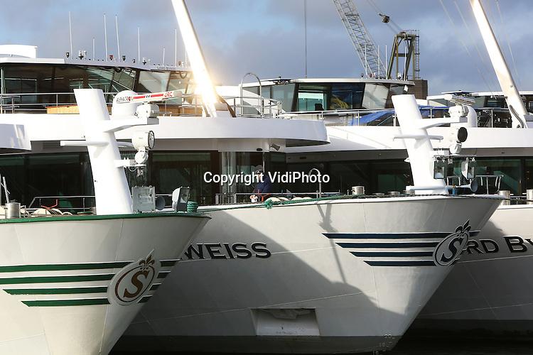 Foto: VidiPhoto<br /> <br /> DODEWAARD - Terwijl diverse scheepswerven het moeilijk hebben of failliet gaan, heeft Shipcon BV in het Gelderse Dodewaard een interessante order binnengesleept. Op de werf langs de Waal ligt op dit moment een tiental luxe cruiseschepen uit Zwitserland. Shipcon mag van de grootste riviercruise-aanbieder van Europa, Scylla AG, het technisch onderhoud verrichten. Dat gebeurt in de winterperiode als er geen cruises zijn. De werkzaamheden aan de varende hotels moeten voor eind maart gereed zijn. Tot die tijd kan Shipcon zo'n 40 mensen aan het werk houden. Voordeel van Shipcon is dat het een relatief grote haven aan de Waal heeft met alle benodigde faciliteiten.