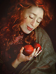 A woman in a scarf , with long red curls and red cheeks and lips, holding a pair of red apples.