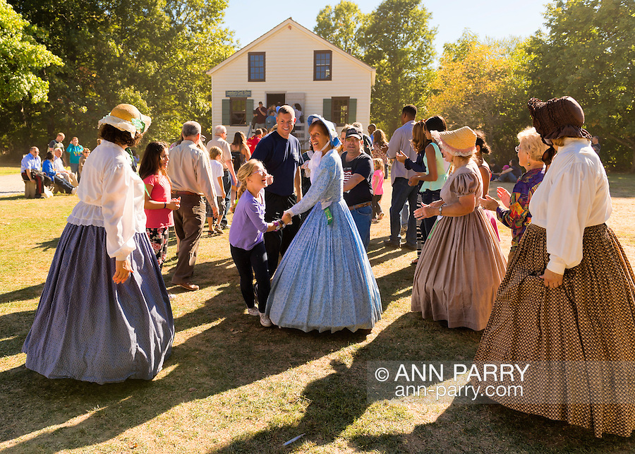 Old Bethpage, New York, U.S. 29th September 2013. The Old Bethpage Dancers are line dancing with visitors at The Long Island Fair. A yearly event since 1842, the county fair is now held at a reconstructed fairground at Old Bethpage Village Restoration.