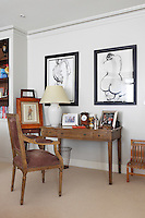 An antique desk and chair provide a spot for letter writing in the corner of a sitting room.