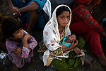 A family, recently displaced from their villages near Jacobabad, holds a mulnourished newborn as thet wait in the hope of receiving food and medical aid at a relief camp on the outskirts of Sukkur.
