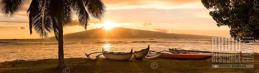 Outrigger canoes at rest on a Maui beach as the sun sets behind Lana'i.