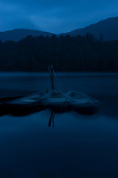 Row boats make ghostly reflections at night on Shirakomaike Lake in the Yatsugatake range, Nagano, Japan