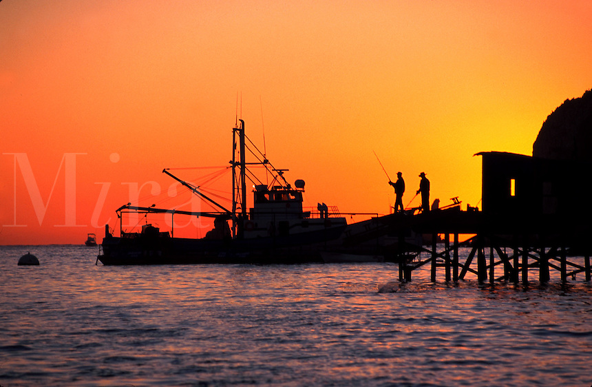Earlt morning silhouette of fishing docks, fishermen and shrimp boat at Cabo San Lucas. Baja, Mexico.