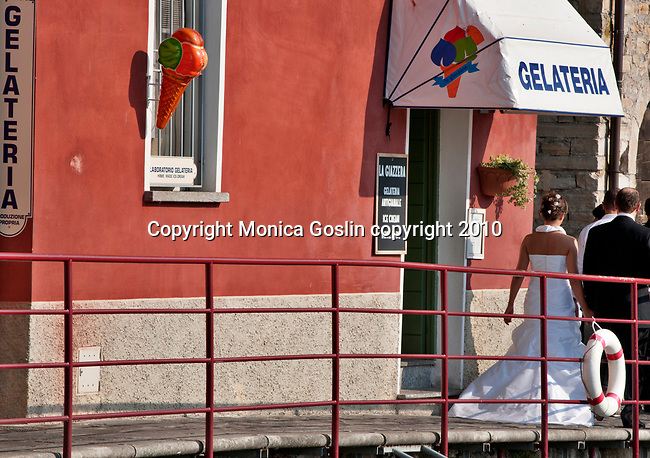 A bride and groom outside a gelato shop in Varenna, Italy on Lake Como