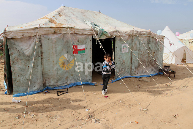 A Palestinian boy stands outside a tent near the ruins of his family's house which witnesses said were destroyed by Israel shelling during a 50-day conflict last summer, east of Khan Younis in the southern Gaza Strip January 27, 2015. The main U.N. aid agency in the Gaza Strip said on Tuesday a lack of international funding had forced it to suspend payments to tens of thousands of Palestinians for repairs to homes damaged in last summer's war. Robert Turner, Gaza director of operations for the United Nations Relief and Works Agency (UNRWA), said in a statement that UNRWA received only $135 million of the $720 million pledged by donors to its cash assistance program for 96,000 refugee families whose homes were damaged or destroyed in the 50-day conflict between the Hamas Islamist movement and Israel. Photo by Abed Rahim Khatib