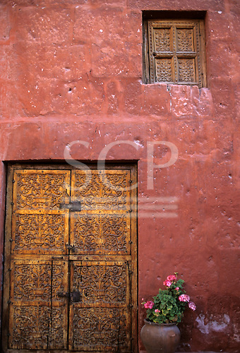 Arequipa, Peru. Carved door and window in a red painted wall with flowers in a pot; Santa Catalina Monastery.