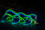 World champion squirt boater, and new women's mystery move record holder Claire O'Hara works on her cartwheels at night on the Truckee River near Reno, Nevada just prior to the world mystery move championships. This concept shoot using glowsticks attached to the athletes squirtboats is designed to show the trajectory and flow of this unique form of kayaking.