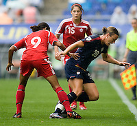 USWNT forward (20) Abby Wambach is fouled by Canada's (9) Candace Chapman during the finals of the Peace Queen Cup.  The USWNT defeated Canada, 1-0, at Suwon World Cup Stadium in Suwon, South Korea.