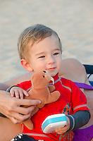 A one-year-old part-Asian boy at a Big Island beach holds a stuffed walrus toy with his mother's help.