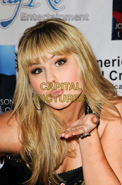 ASHLEE KEATING .Arriving at a Pre-Grammy party to benefit the American Red Cross, Santa Monica Chapter, at H.Wood Nightclub in Hollywood, California, USA,.January 29th, 2010 .portrait headshot fringe hand blowing kiss  black .CAP/ROT.©Lee Roth/Capital Pictures.