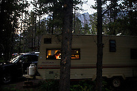 A man sits in a camping trailer in the Many Glacier campground in Glacier National Park in Montana.