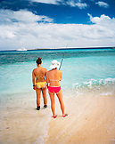 FIJI, Northern Lau Islands, two young women fishing by the waters edge on a remote island in the South Pacific