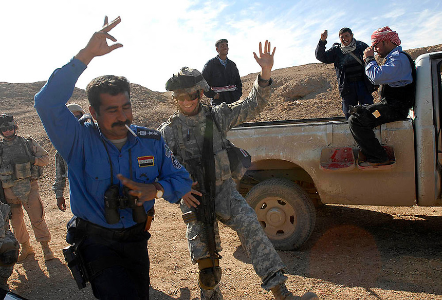 A U.S. soldier celebrates the discovery of a weapons cache with a Iraqi Police commander outside of Ramadi, Iraq. (James J. Lee / Army Times)