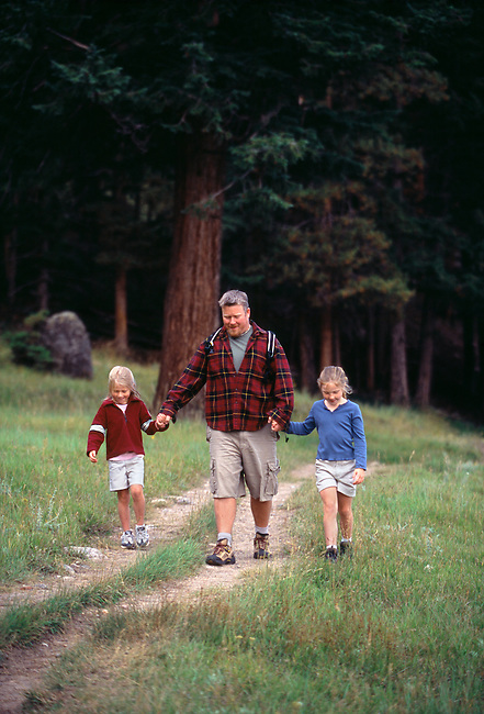 A dad and his daughters hike along a trail at the forest's edge in Rocky Mtn Nat'l Park, CO
