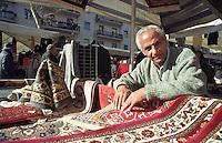 Milano, mercato rionale di viale Papiniano. Venditore di tappeti originario dell'Africa --- Milan, local market in Papiniano street. Carpet vendor native of Africa
