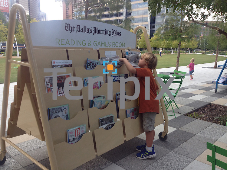 10/11/13 Travers Edwards (6 yrs.) looks through the reading material at The Dallas Morning News Reading and Games Room at Klyde Warren Park.