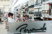 An employee works on a Personelle products display at a Jean Coutu Pharmacy in Quebec city March 4, 2009. Personnelle is the home brand of Jean Coutu Group (PJC)