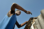 A man works building a temporary home in a camp for homeless families in the Belair section of Port-au-Prince, Haiti. The country was wracked by a devastating earthquake on January 12, 2010.