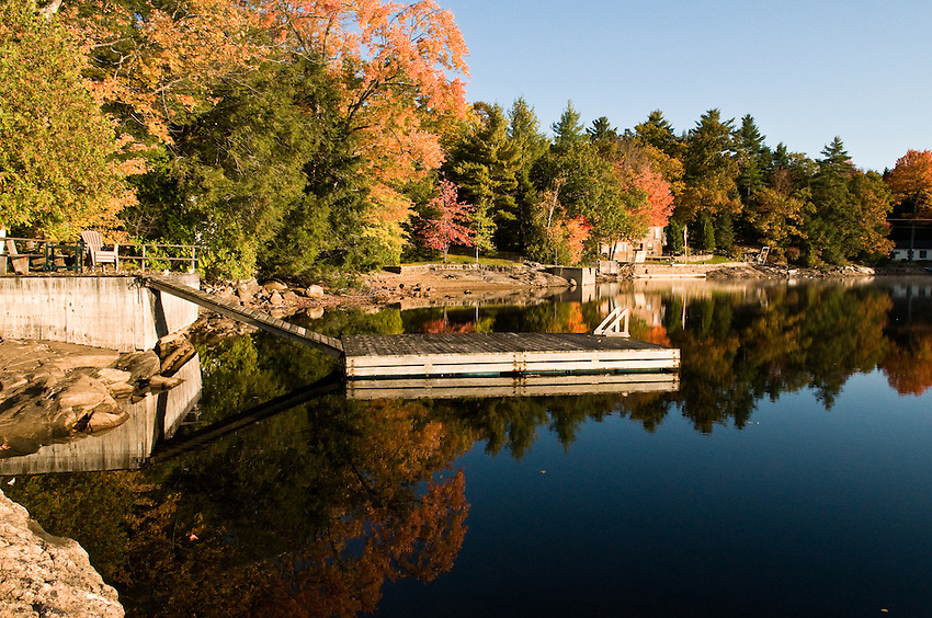 Mississauga Lake reflection with boat dock, fall colors and lakefront homes in the distance.